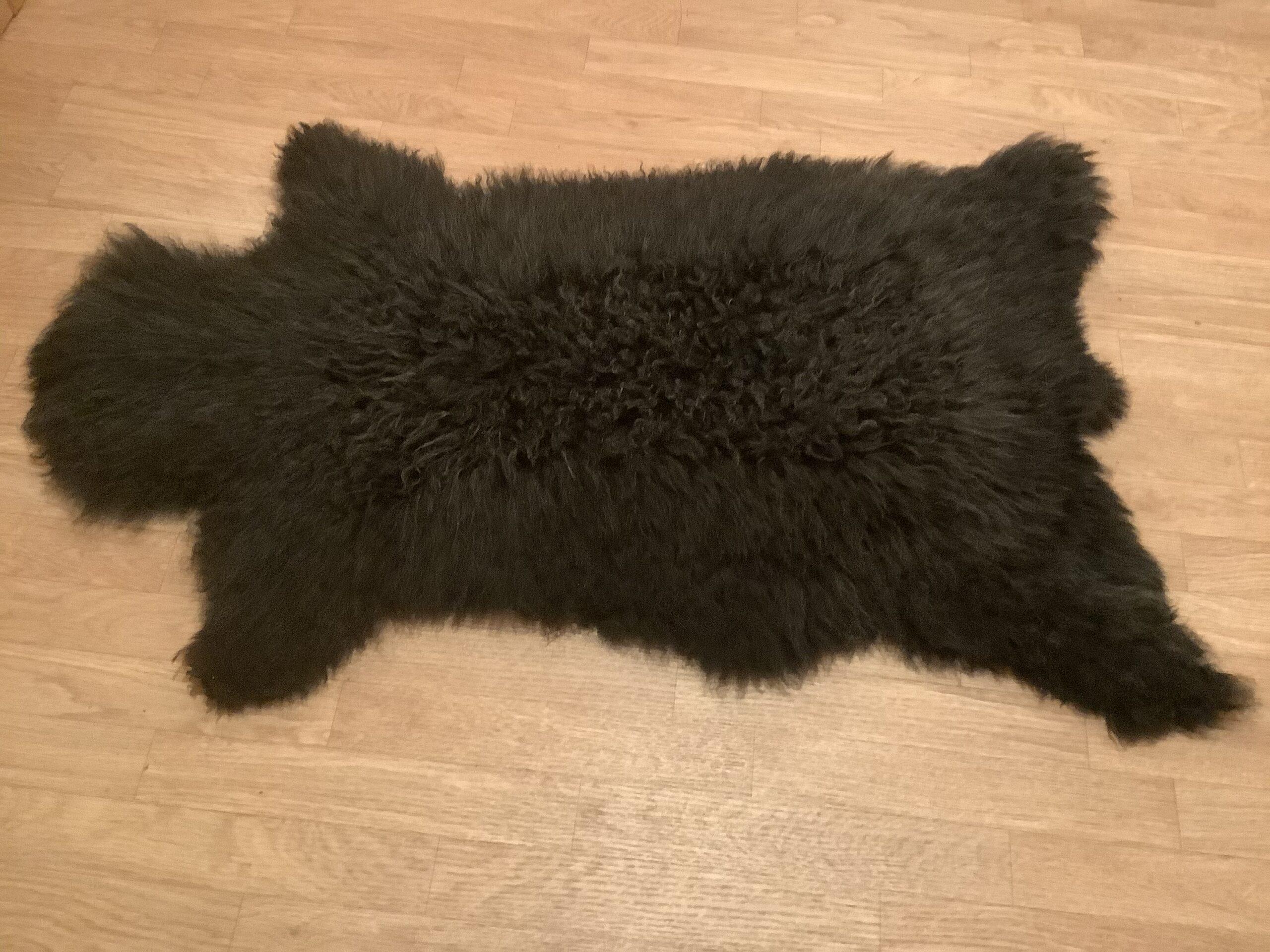 Black sheep skin rug